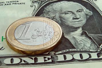 Euromünze auf Dollarschein