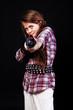 Portrait of beautiful girl posing in studio with gun