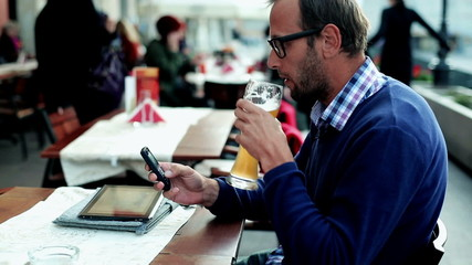 Young man with tablet and cellphone drinking beer