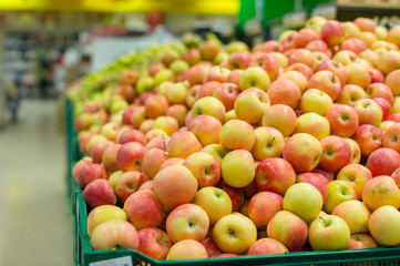 Bunch of red and green  apples on boxes in supermarket