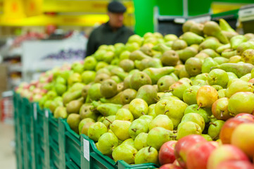 Bunch of green pears on boxes in supermarket