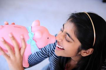Indian girl holding piggybank