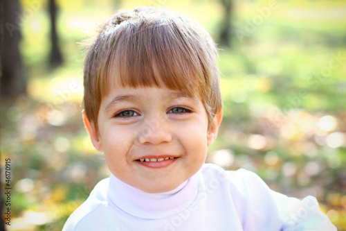 Smiling little boy in the autumn forest