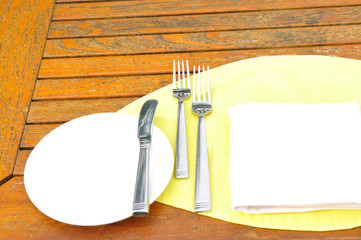 fork knife and spoon on white plate and yellow napkin