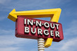 A classic IN-N-OUT BURGER sign in front of sky with yellow arrow