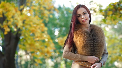 Young Woman Wearing Fur Vest in the Autumn Park