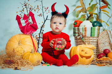 Adorable toddler in red halloween costume of devil