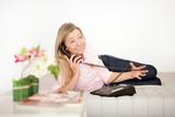 Frau überlegt auf der Couch mit Telefon