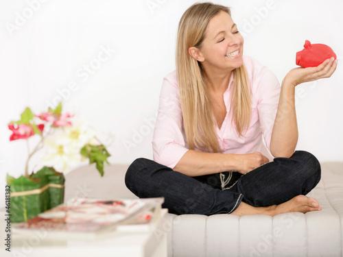 Frau mit Sparschwein auf der Couch