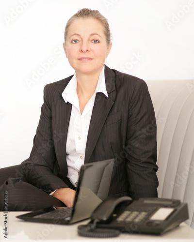 Frau mit Laptop und Telefon