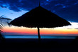 Silhouette of Parasol on a beach over Sunset