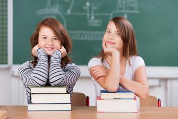 zwei schülerinnen mit büchern im klassenzimmer