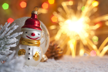 Snow man and blurred christmas background with sparklers