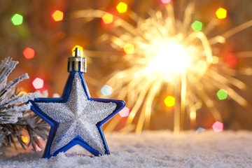 Christmas star on snow and blurred  background with sparklers
