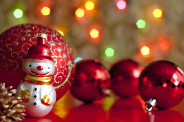 Snow man and baubles against blurred colorful background