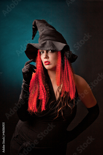 Witch practises witchcraft on black background.