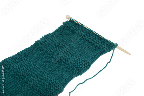 Scarf on knitting needles in stocking and garter stitch