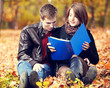 Beautiful couple with notebook at autumn park.