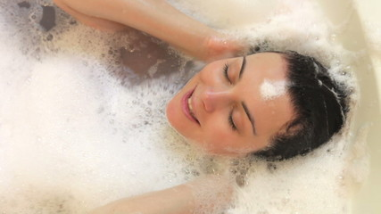 Overhead View Of Woman Washing Hair In Bubble Filled Bath