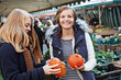 two young women looking at Hokkaido pumpkins