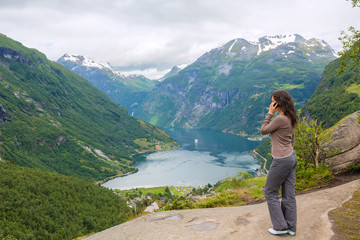 Young girl talking on a cell phone on a cliff edge