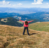 Woman tourist on the mountain with raised hands feeling success