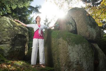 Frau bei Entspannungsübung zwischen Felsen