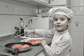 Un pequeño cocinero muy simpático y divertido en la cocina