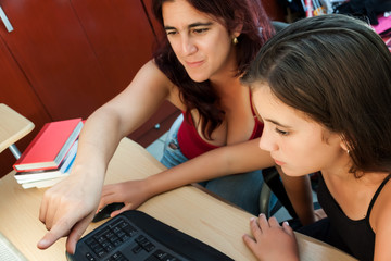 Latin mother teaching her young daughter how to use a computer