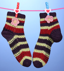 Pair of knit striped socks hanging to dry over blue background