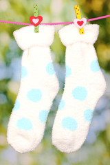 Pair of socks with polka dots hanging to dry