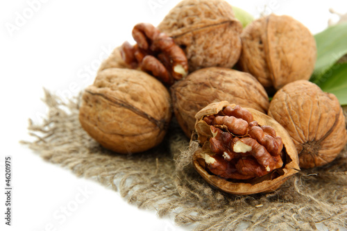 walnuts with green leaves on burlap, isolated on white