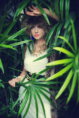 Lady in a fur hat in the jungle, fashion portrait.