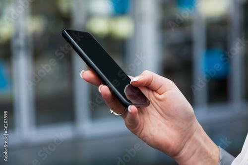 Frau schreibt SMS am Flughafen