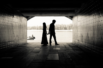 Silhouette of a couple on bright background in a tunnel