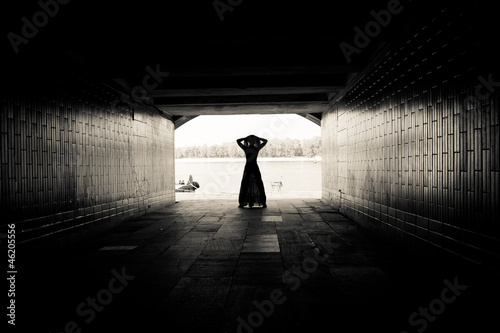 Silhouette of a girl on bright background in a tunnel