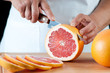 Horizontal shot of a woman cutting a grapefruit