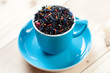 Turquoise cup with black tea leaves on wooden boards
