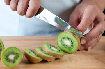 Senior woman cutting kiwi fruits, studio shot