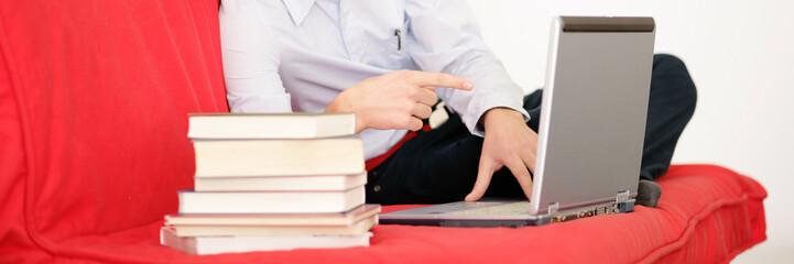 Junge liegt auf der Couch mit Büchern und Laptop
