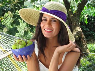 Joven mujer comiendo uvas.Mujer fruta en un jardín.