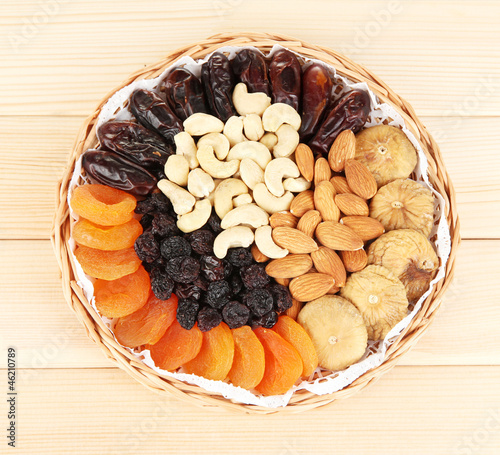 different dried fruits on wooden background