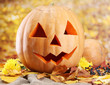 halloween pumpkins and autumn leaves, on yellow background