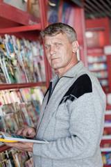 mature man looks the magazine in a bookshop