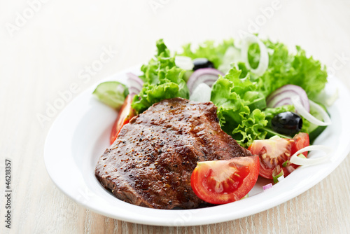 Grilled steak with fresh vegetables on a plate