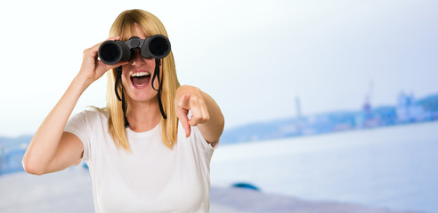 woman looking through binoculars and pointing