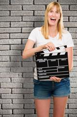 pretty woman holding a clapper board