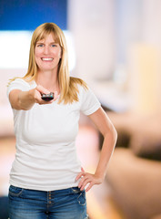 Portrait Of A Happy Woman Holding Remote Control