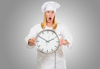 Shocked Female Chef Holding Clock
