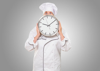 worried chef hiding behind a clock